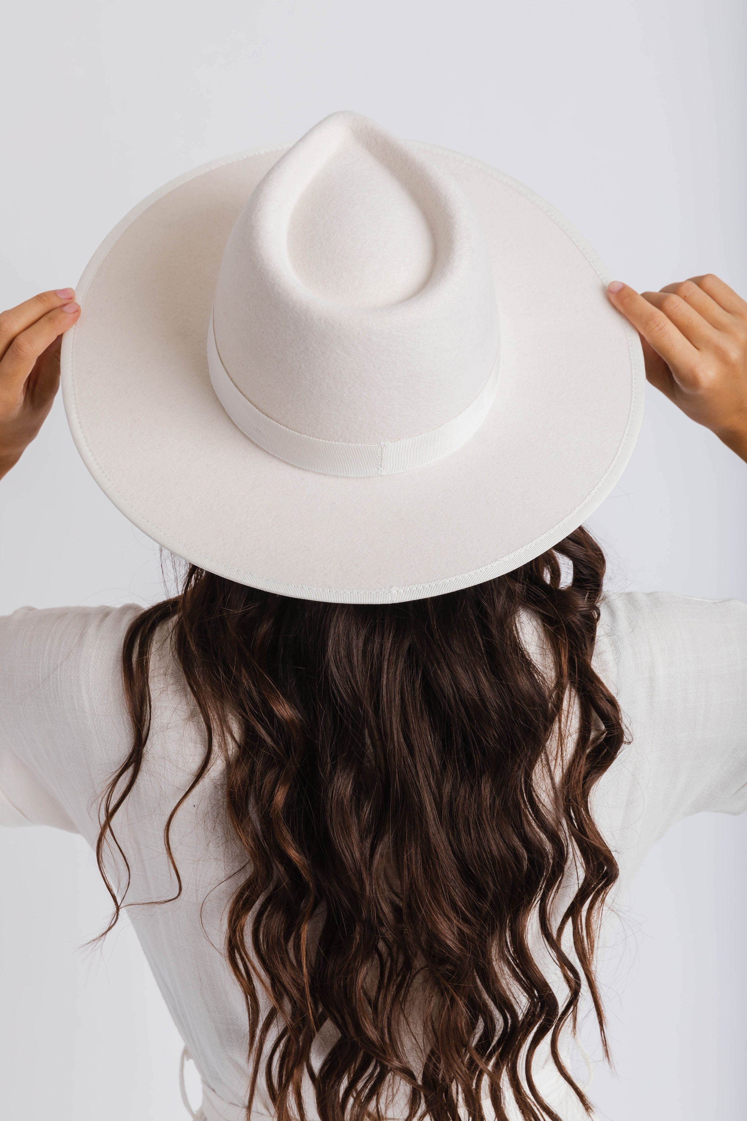 The Rae is a women's stiff ivory fedora with a tonal grosgain ribbon trimmed on the crown and the brim.