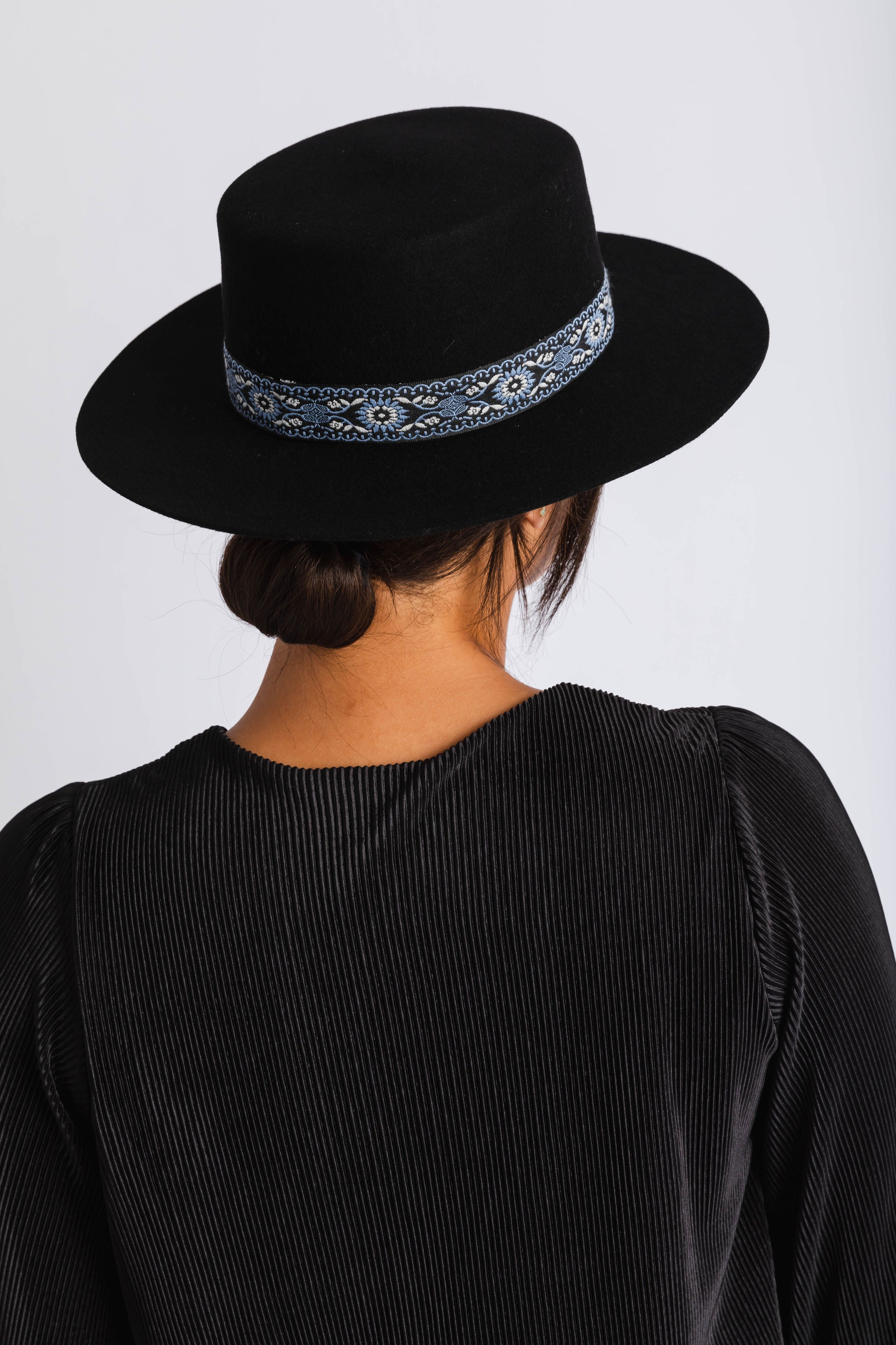 The Dakota is a women's black boater with patterned ribbon trimmed on the crown.
