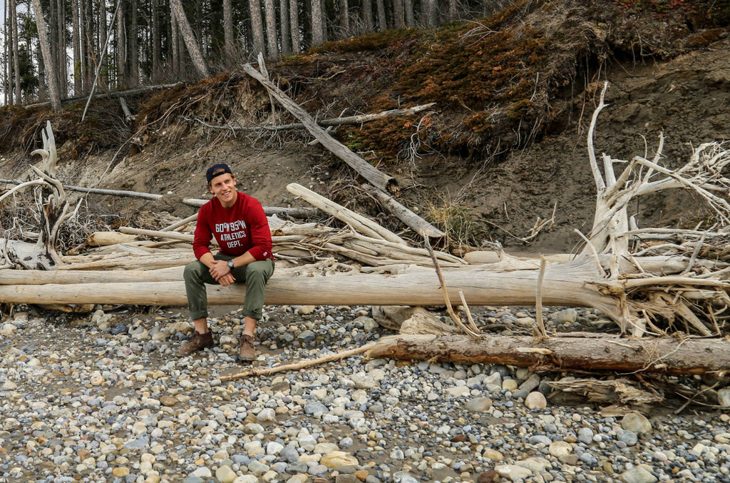Man sitting down on a log wearing a harvest red long sleeve t-shirt