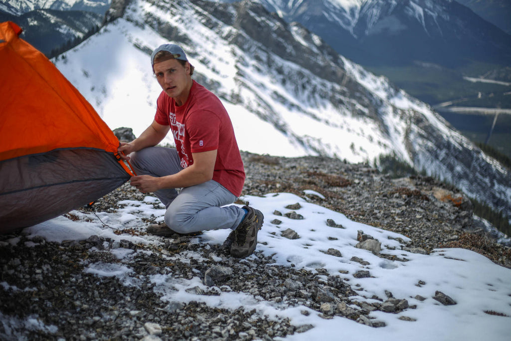 Man fastening a tent wearing a faded red t-shirt looking at the camera