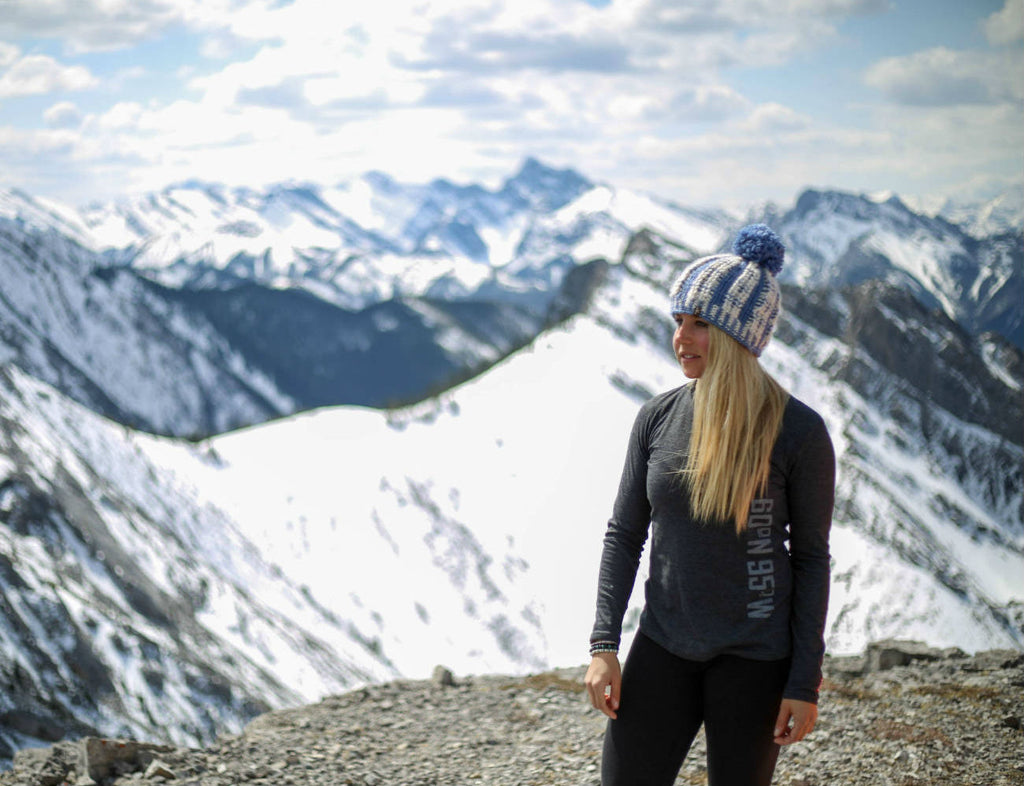 Girl standing on top of snow covered mountain admiring the view