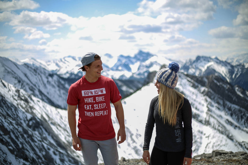 Girl and guy standing on top of a mountain wearing 60°N 95°W clothing smiling at each other