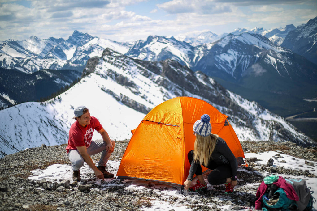 Girl and guy crouched down fastening their tent on top of a mountain