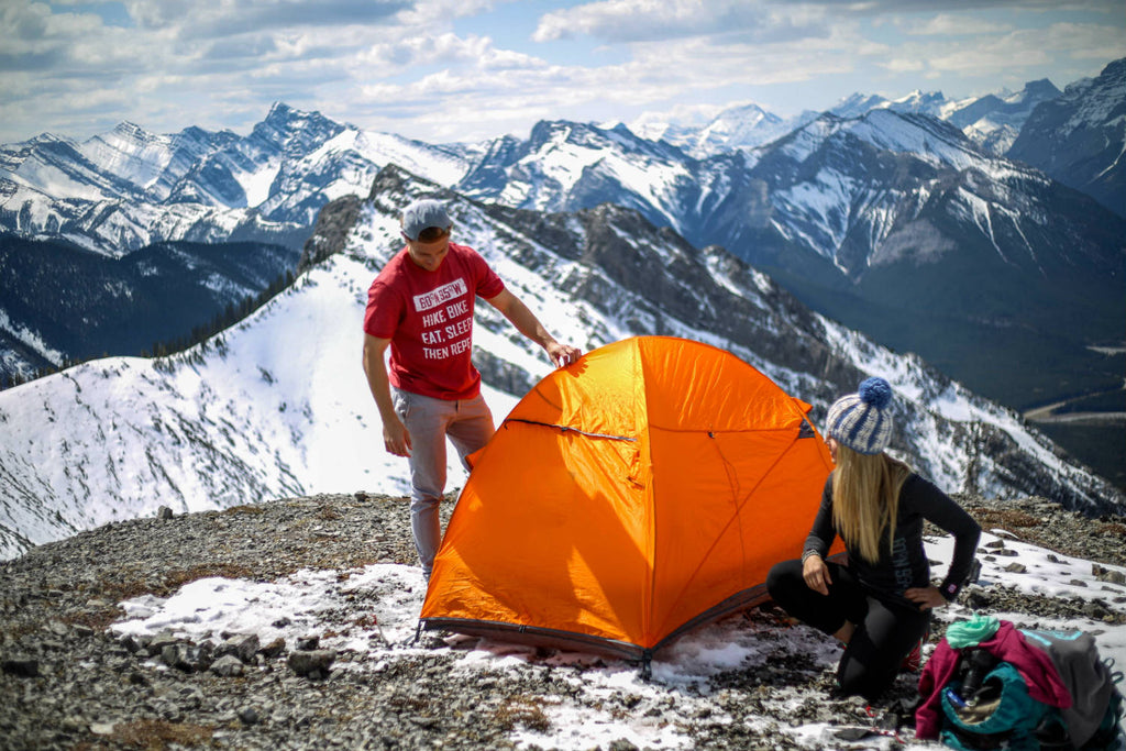 Girl and guy finishing pitching their tent and admiring their work