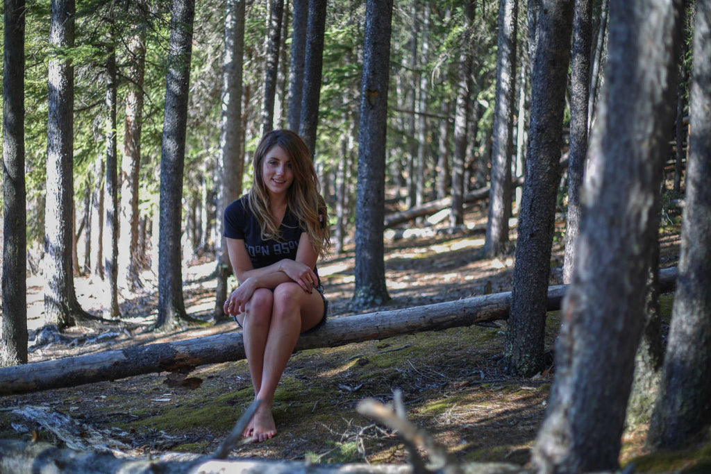 Girl wearing a 60°N 95°W black v-neck t-shirt sitting on a falled tree in the forest smiling at the camera