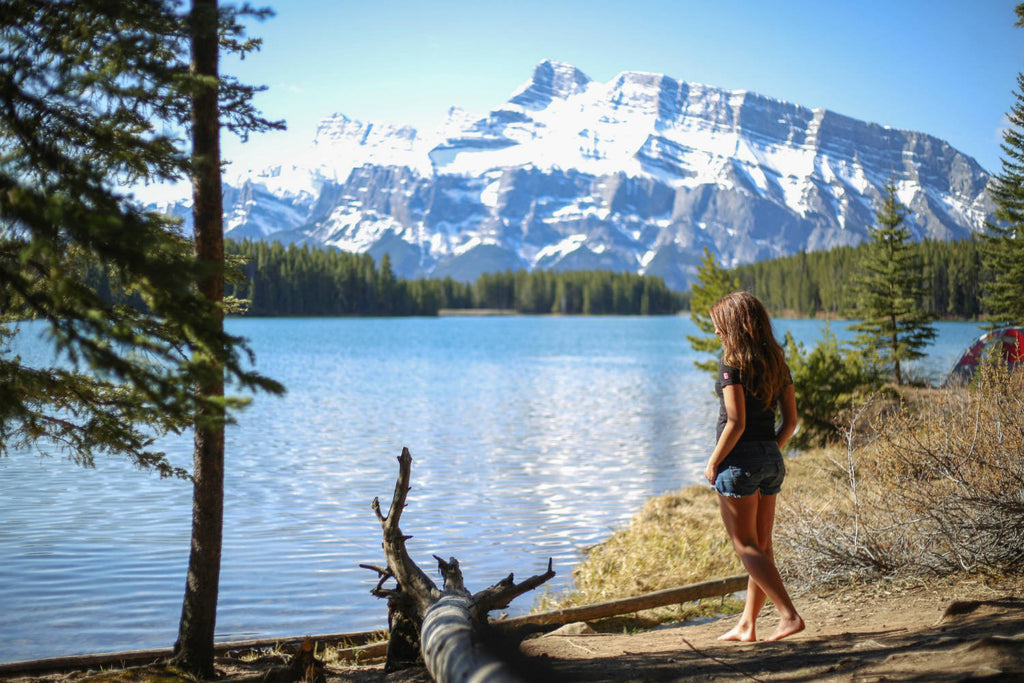 Girl wearing a black v-neck t-shirt standing by a lake admiring the view