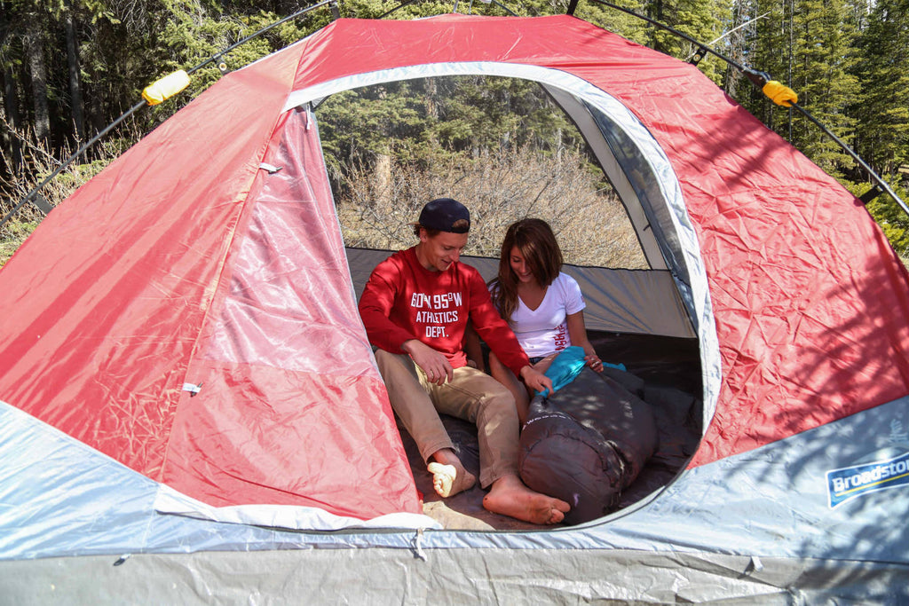 Girl and guy sitting inside a tent wearing 60°N 95°W clothing