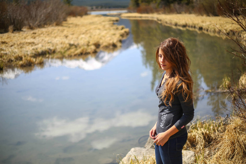 Girl wearing a black mix 5-button henley standing by a river