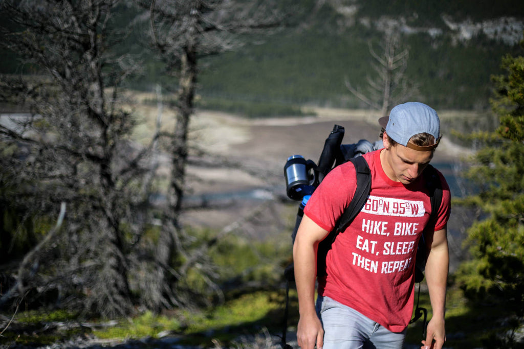 Man wearing a faded red t-shirt walking up a rocky mountain