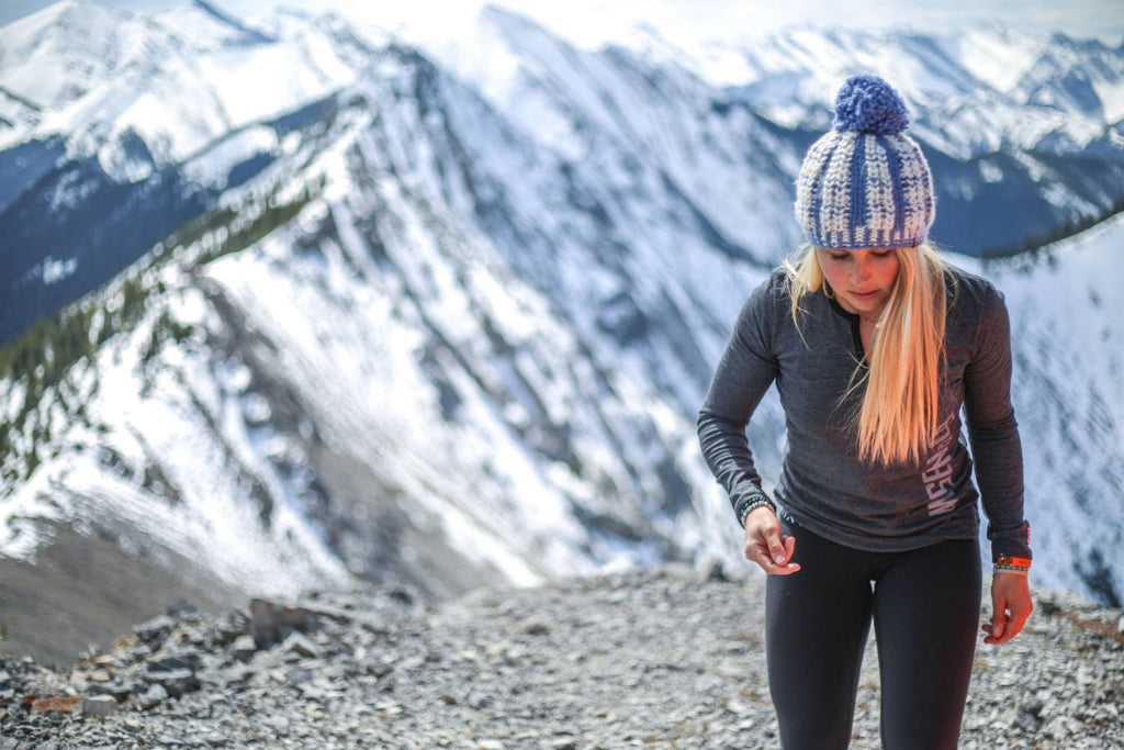 Girl walking up a snow covered mountain wearing the black mix 5-button henley