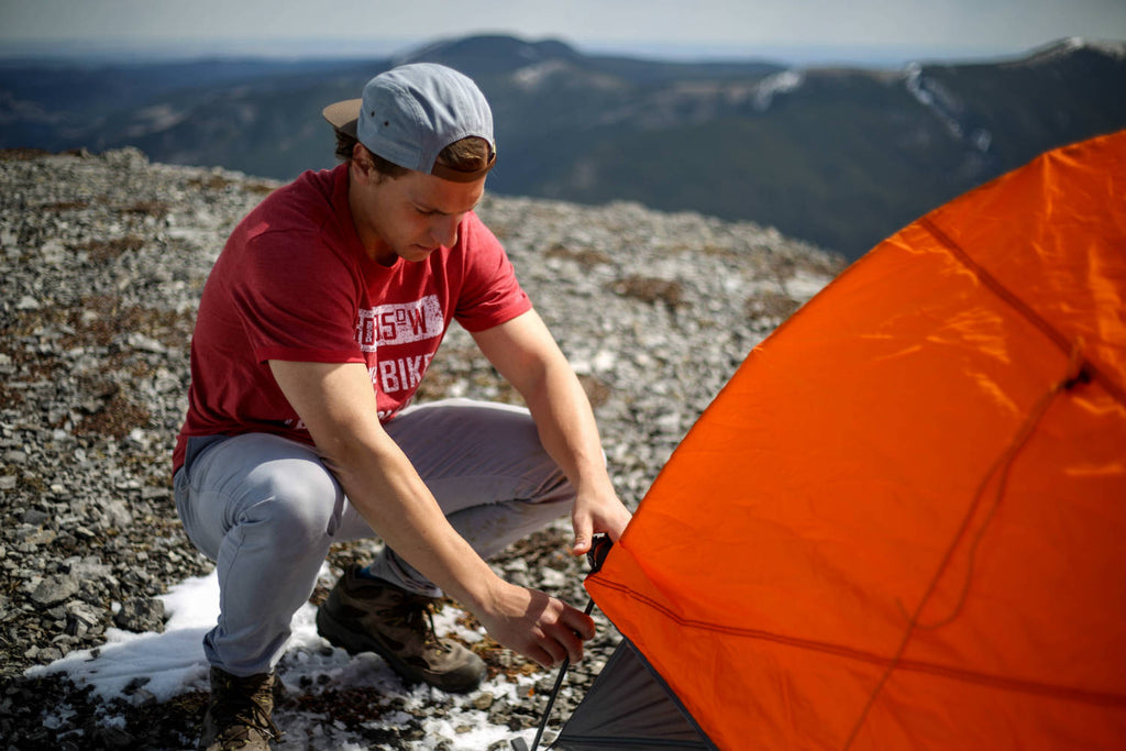 Man crouched down pitching a tent wearing a Hike, Bike, Eat, Sleep t-shirt