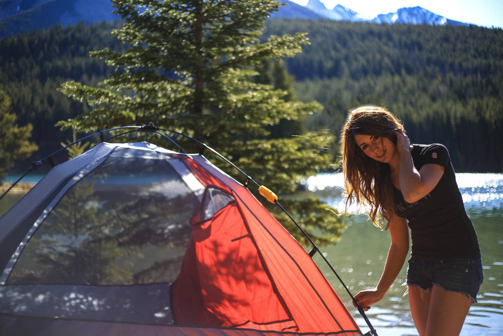 Girl wearing a black v-neck t-shirt leaning over her tent