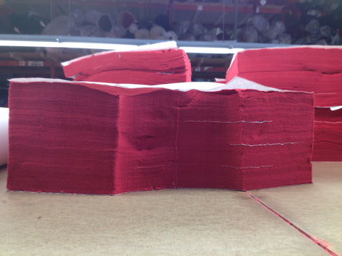 Stack of 100% cotton fabric that's been cut into panels.