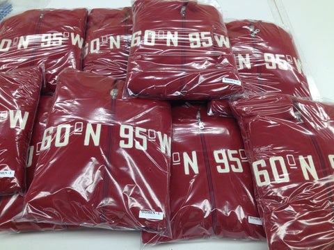 A stack of 60°N 95°W women's hoodies in clear packaging.
