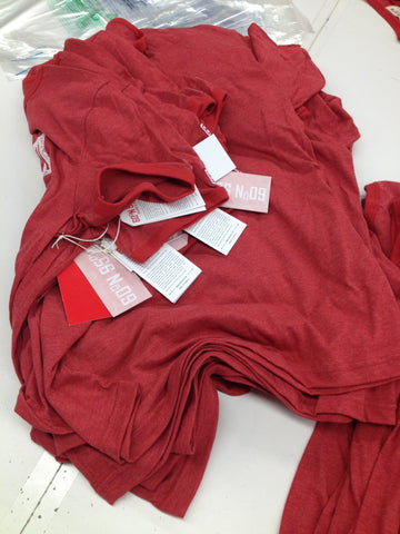 A stack of 60°N 95°W t-shirts with hang tags.