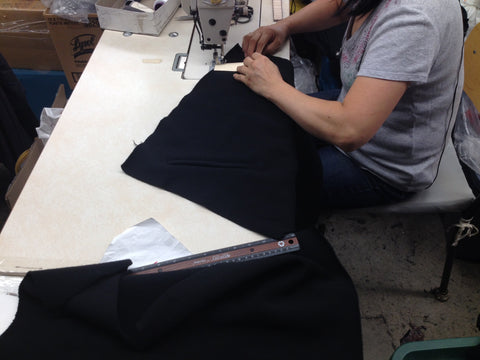 A seamstress sews a fleec sweater with precision.