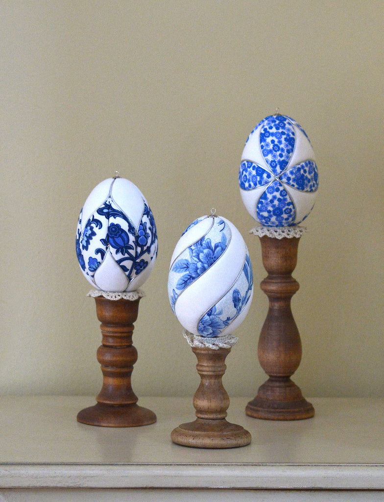 three blue and white kimekomi Easter eggs on candle holders as egg stands