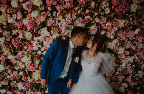 Happy wedding couple against flower wall