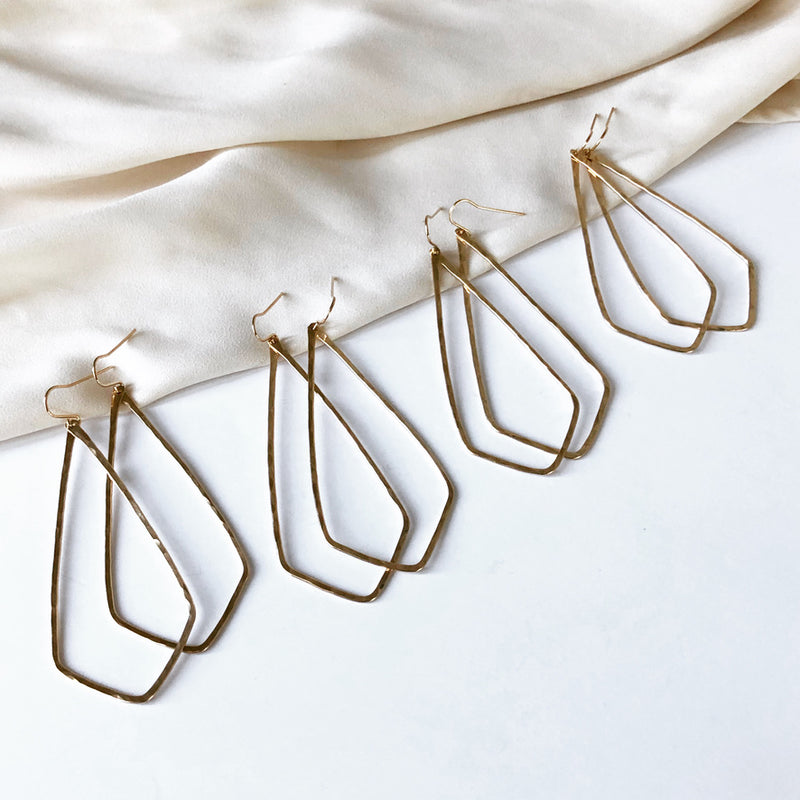 four pairs of handmade, diamond shaped gold earrings, set on a cloth background