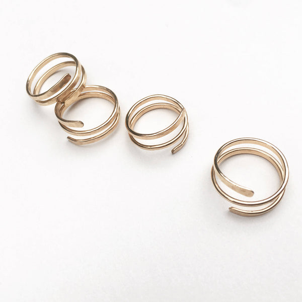 four, handmade, gold wire wrap rings, placed on a white background