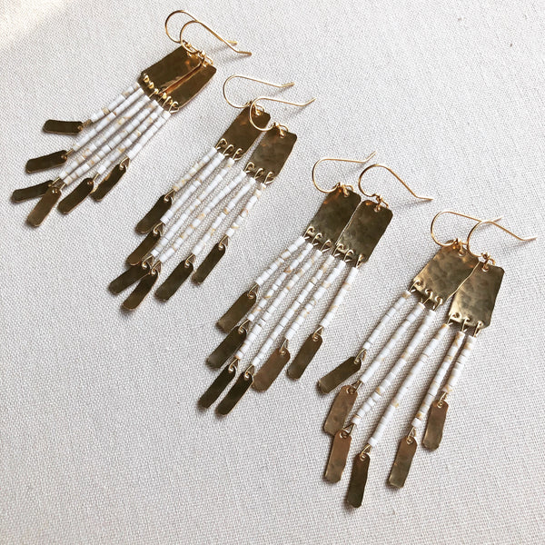 beaded earrings featuring white magnesite stones and brass tassels, on a white background