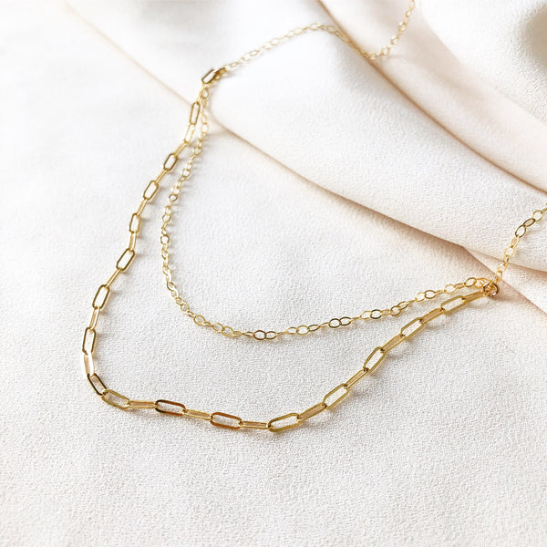 gold filled chain necklace on a white fabric background, paper clip chain and cable chain gold filled necklace