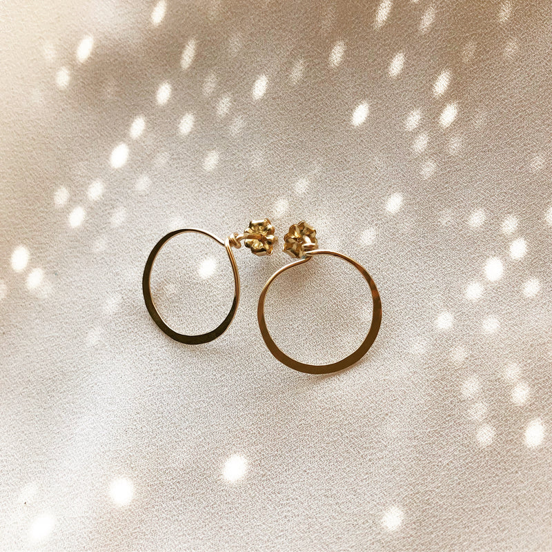 handmade earrings that are gold circle stud earrings, placed on a white background