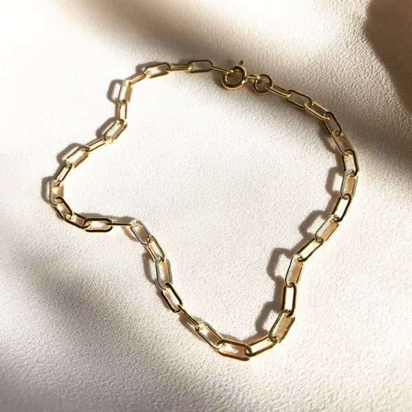 gold, paper clip chain bracelet laying in the sunlight