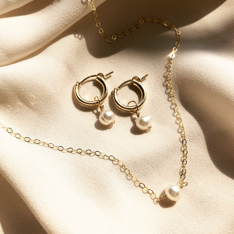 gold hoop, pearl earrings and a matching gold pearl necklace, placed in the sunlight on a white fabric