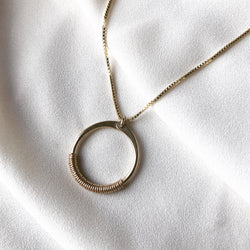 handmade open circle necklace with wire wrap detail,  pictured here is gold