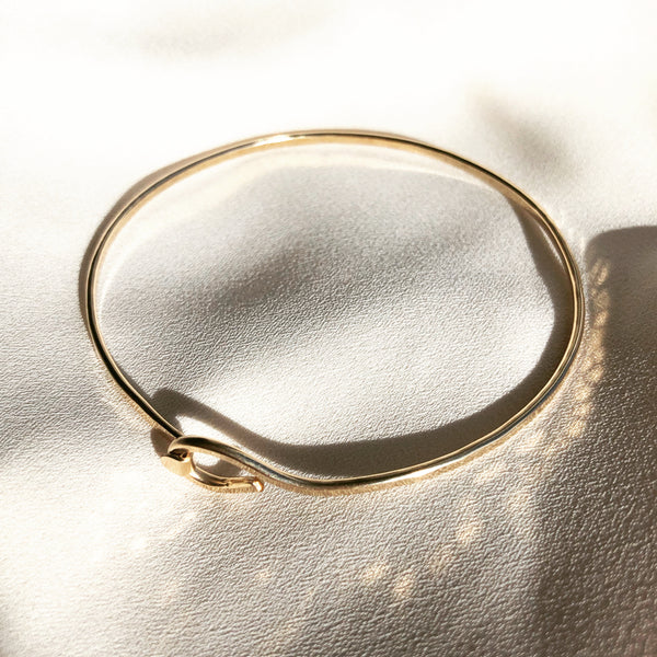 14k gold filled, handmade bangle, placed on a white fabric background.