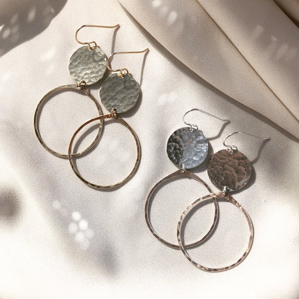 handcrafted hoop earrings with hammered discs, in gold filled and sterling silver, laying in the sunlight
