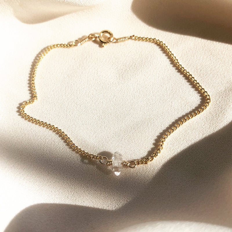 14k gold filled bracelet with herkimer diamond detail laying on a white fabric with sunlight