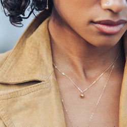 Gold filled ball necklace on black woman model, wearing leather jacket