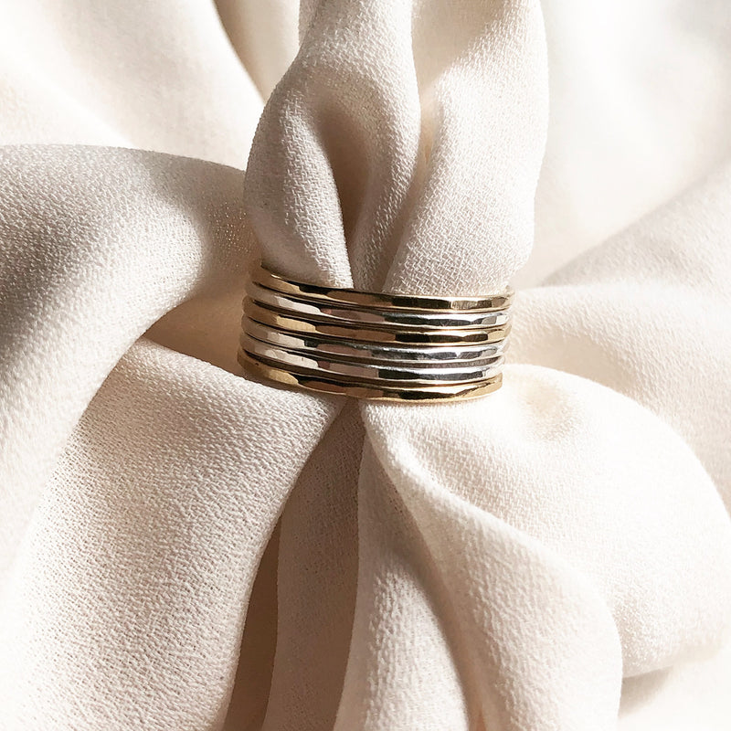 handmade gold and sterling silver stacking  rings, placed on a piece of fabirc