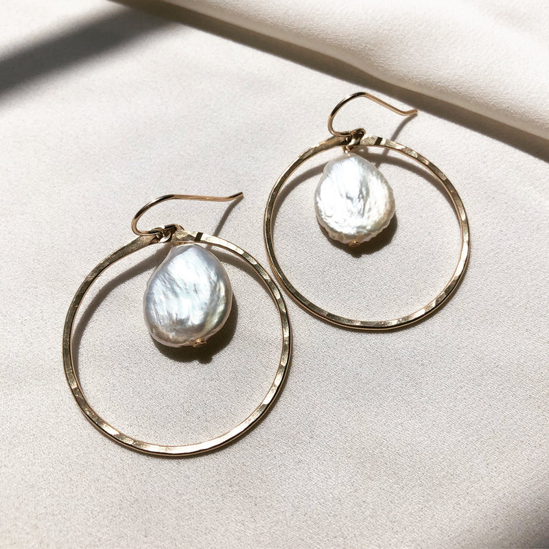 handmade, freshwater pearl earrings with gold hoops, displayed on a fabric background