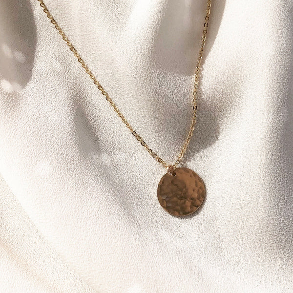 handmade, gold coin necklace on a gold chain, laying in the sunlight