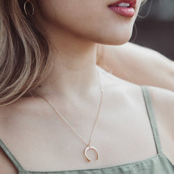 young woman wearing a gold, crescent moon necklace, and matching moon earrings