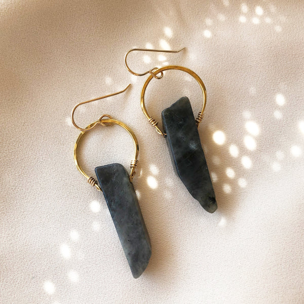 black labradorite stone earrings with gold hoops, placed on a white background with sunlight spots in the background