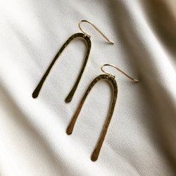 handmade, hammered earrings which are gold arc earrings displayed on a white background
