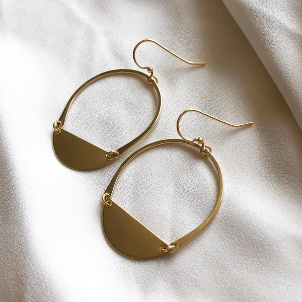 brass hoop earrings with crescent moon detail, laying on a white cloth background