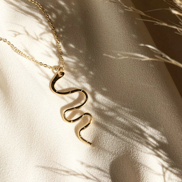 gold snake serpent necklace hangs from a gold filled chain