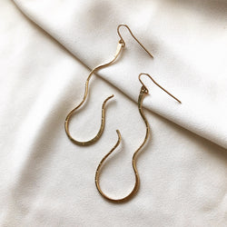 handmade, gold earrings that resemble a snake or flowing water, on a white background