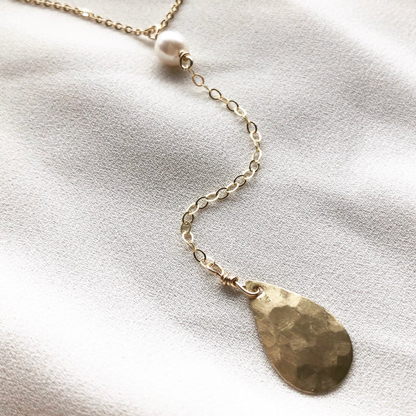 14k gold-filled chain lariat necklace with  drop detail featuring freshwater pearl and gold water droplet , on a cloth background