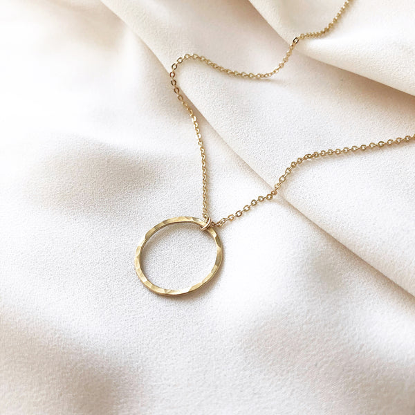 handmade gold circle necklace, on a gold filled chain, laying on a white fabric background