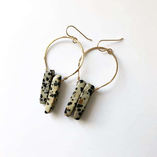handmade earrings, gold earrings which hold a Dalmatian jasper stone, placed on a white background