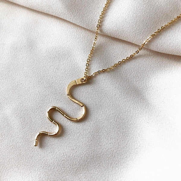 gold snake serpent necklace hangs from a gold filled chain, on a white fabric background