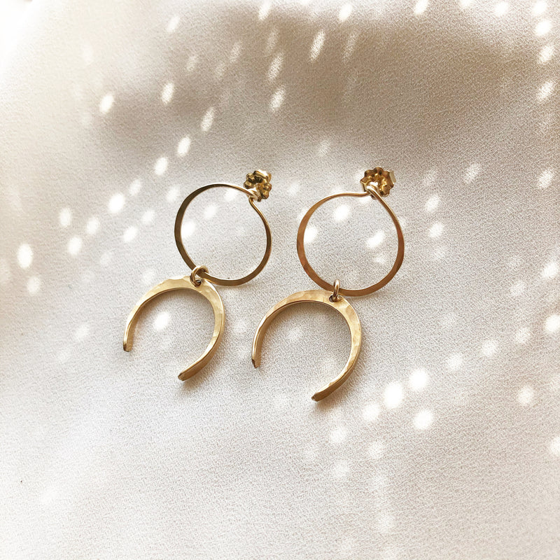 Open circle stud earrings with crescent moon detail, laying on a white background
