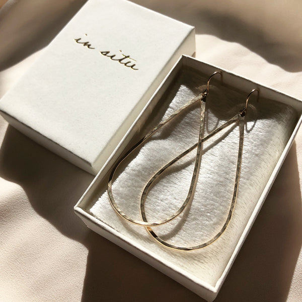 handmade, large gold hoop earrings laying in a jewelry box