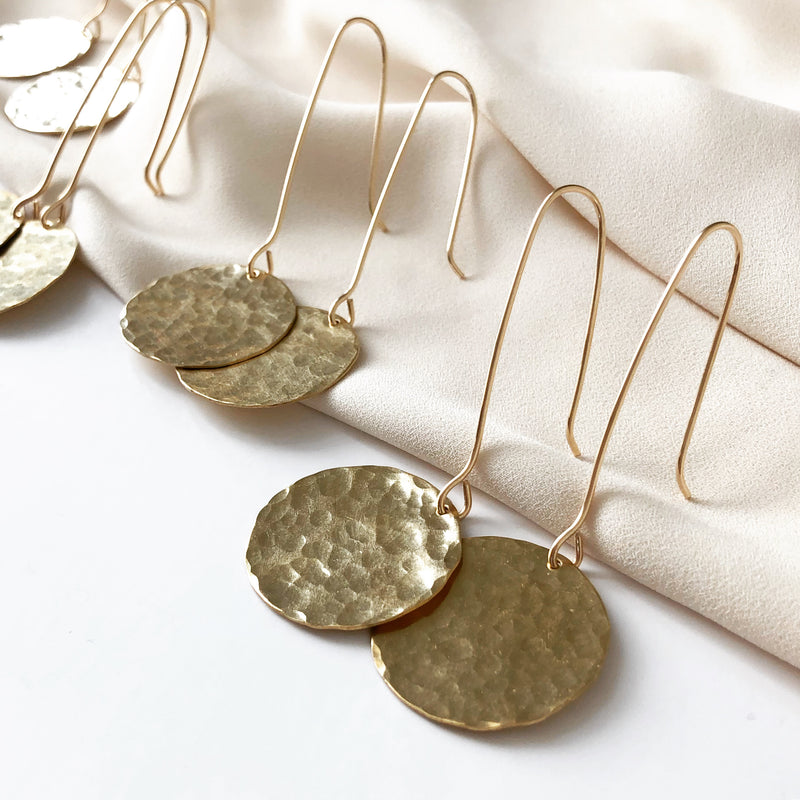 handmade earrings, large gold disc earrings which resemble a full moon, resting on a white fabric